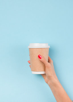 Cup of coffee to go and woman hand with manicure, blue pastel