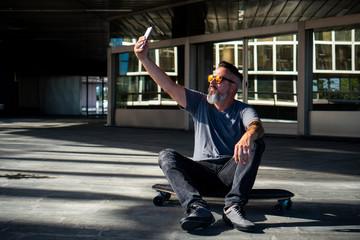 Skater taking a selfi on a skateboard