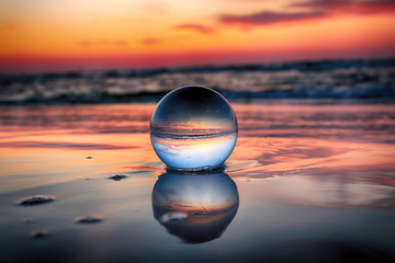 Papiers peints Gris traffic Beautiful sunset on the beach in Slowinski National Park near Leba, Poland. View of a starfish through a glass, crystal ball (lensball) for refraction photography. Wild, untouched nature.