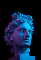 Gypsum copy of ancient statue Apollo head isolated on black background. Plaster sculpture man face.