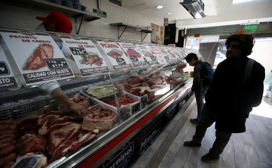 Costumers are seen at a butcher shop in Buenos Aires