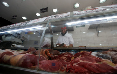 A butcher chops meat at his shop in Buenos Aires