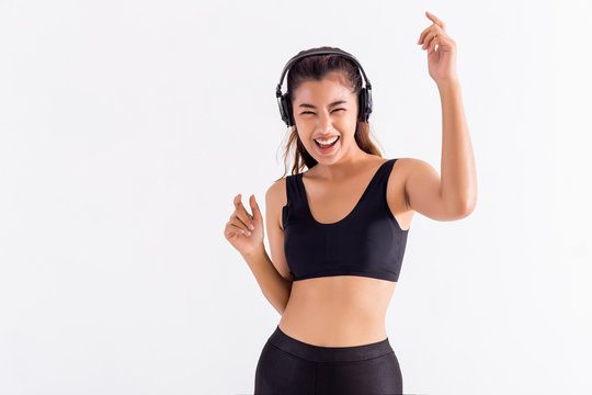 Happy Asian woman in black sport bra listening to music and dancing with raised hands on white background. One girl moving in studio shot