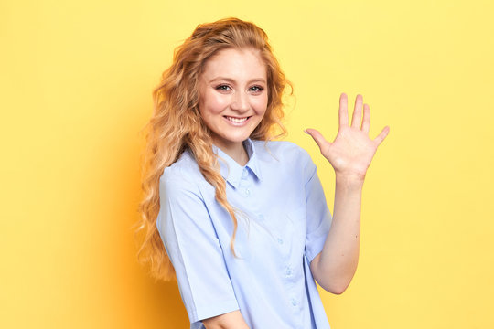 cheerful charming positive beautiful young woman smiling happily, saying Hello, Hi or Bye, waving hand at camera. Greeting, goodbye and body language, isolated yellow background