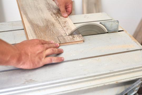 Carpenter on work putting laminate wood. Home construction..