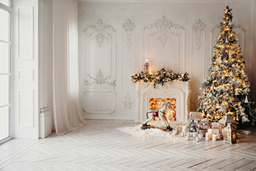 classical luxury interior of a white room with Christmas tree with garland, decorated fireplace, rocking horse, gifts for new year