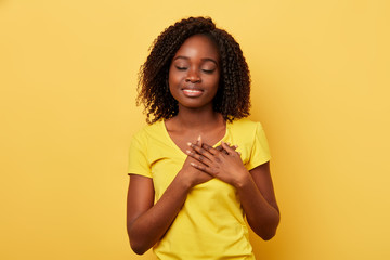 emotional calm woman with closed eyes, keeps hands on chest, expresses her sympathy to someone, being thankful to somebody. close up photo. isolated yellow background, feeling and emotion concept