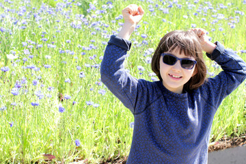 thrilled young girl with blue sunglasses over spring cornflower field