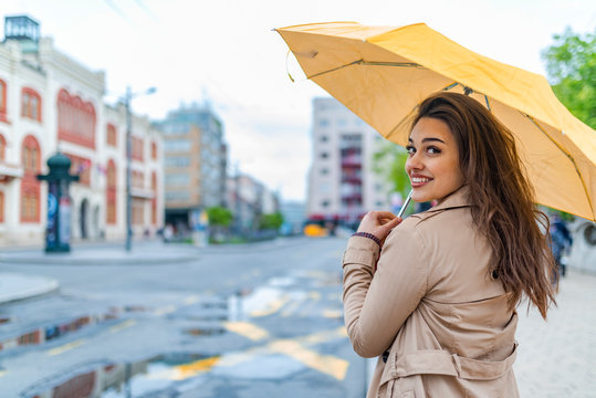 Feeling dry and protected. Portrait of laughing happy woman under an umbrella near the city centre.  It's spring rain. Attractive young woman walking in the street under the rain.
