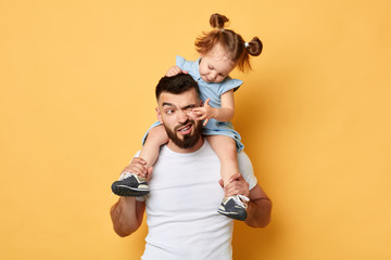 naughty behavior. parent cannot handle with kid with much energy. girl tiuching her dad's eyes while sittting on shoulders . close up photo. isolated yellow background. unacceptable kind of behaviour