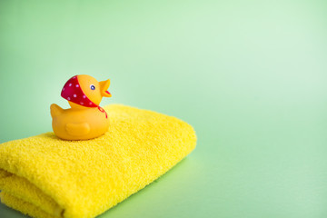 Yellow bath towel and rubber duck green background. Copy space.