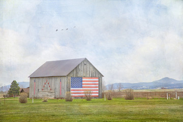 Original textured photograph of an old barn with an American flag on the front