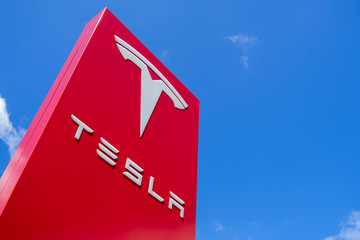 ROTTERDAM, THE NETHERLANDS - June 21, 2018: Tesla dealership sign against blue sky