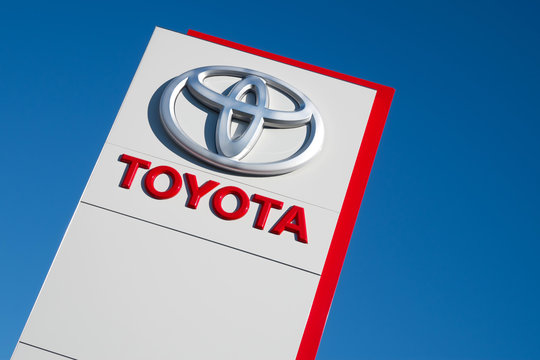 COLOGNE, GERMANY - August 25, 2016: Toyota dealership sign against blue sky. Toyota is the world's market leader in sales of hybrid electric vehicles.