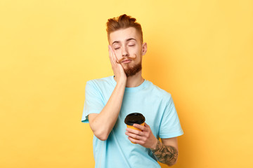Tired exhausted guy with sleepy expression, covers face with palm, holds disposable paper cup of coffee. isolated yellow background