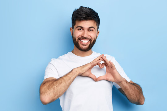 handsome cheerful guy is making a heart shape symbol with his fingers, expresses love and positive romantic feeling. Isolated on a blue background, positive man