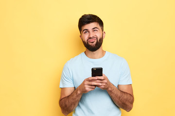 brunette handsome puzzled hesitated man using smartphone isolated over yellow background, thoughtful man doesn't want to answer the message Wall mural