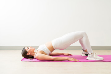Attractive Woman With Setu Bandha Sarvangasana At Yoga Studio