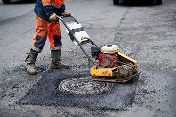 Construction worker in uniform operate vibratory plate compactor. Pothole repair process. Asphalt tamping machine operator. Pothole patching and repair. Laying asphalt around the hatch. New asphalt