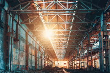 Ruined and abandoned industrial factory warehouse hangar in sunset light, Wall mural