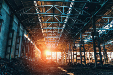 Foto op Plexiglas Oude verlaten gebouwen Ruined and abandoned industrial factory warehouse hangar in sunset light,