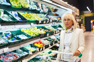 Elegant, good looking senior woman doing shopping in a supermarket. Mature woman with a cart filled with groceries in front of the shelves with fruit and vegetables.