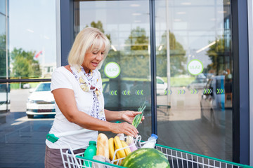 Senior woman with a cart filled with groceries in front of the supermarket. Mature woman checking the groceries in a shopping cart.