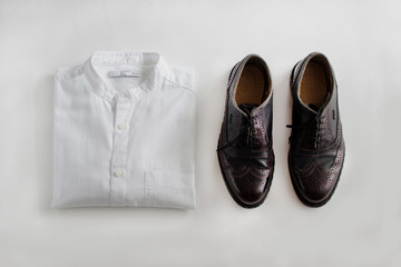 Male outfit set on white background. Shirt and shoe. Close-up, top view