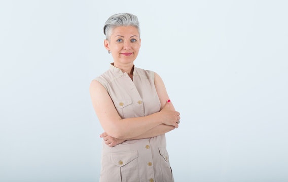 Portrait of a beautiful mature woman on a blue light background. Female middle age with gray hair.