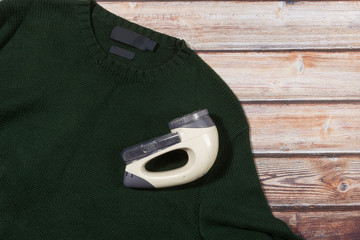 wool sweater with electric lint remover on wooden background