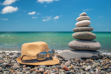 A cairn of stones near the sea, next to a straw hat and glasses. Stone tower on the beach on a sunny day. Balance, peace of mind.