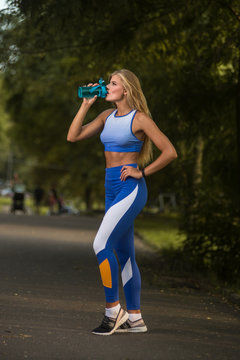 Young attractive sporty woman drinking water during exercise break. Great body.