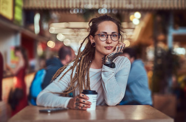 Beautiful cheerful girl with tattooes and dreadlocks is sitting at food court while drinking coffee.