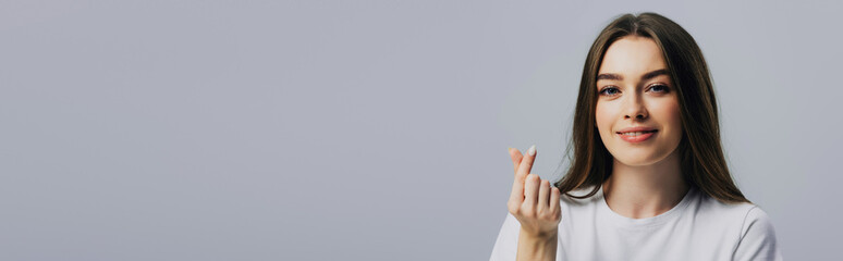 panoramic shot of beautiful smiling girl showing money gesture isolated on grey