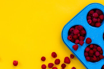 Raspberries on yellow background. Close up, top view