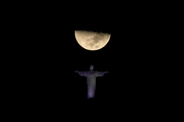 Corcovado statue iluminated at night with the First Quarter Moon right behind it