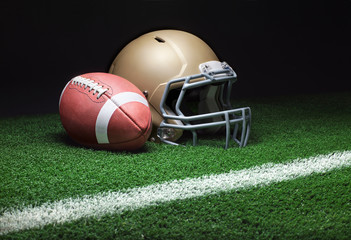 A gold football helmet and a football on a grass field with stripe on dark background