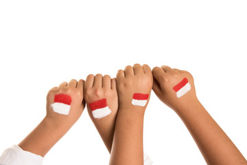 Childrens hands making fist with red and white Indonesian flag painted - Indonesian Independence day national holiday concept image.