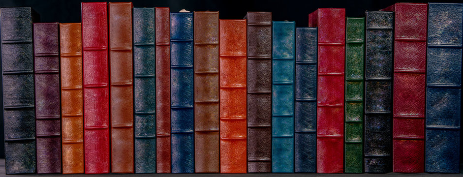 A stack of beautiful leather bound books with a black background.