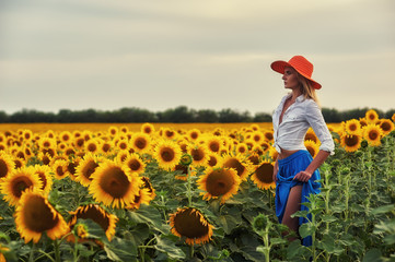 A young woman in a wide-brimmed hat in a field with a flowering sunflower .