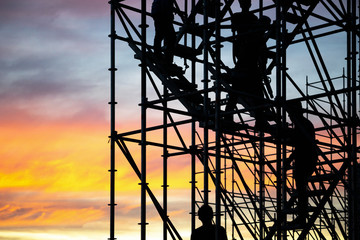 The workers are climbing the silhouette of scaffolding in the high altitude, horizontal and...