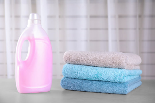 Clean towels and bottle of laundry detergent on table against blurred background