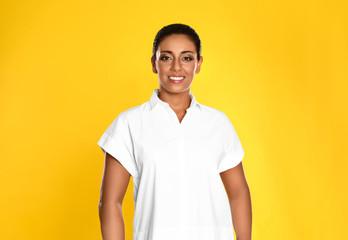 Beautiful Hispanic woman posing on yellow background