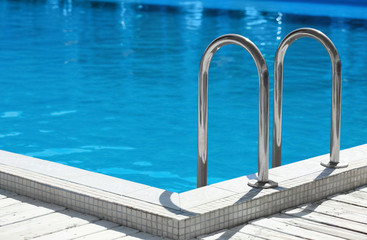 Modern swimming pool with step ladder outdoors