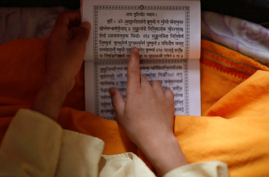 A young Hindu priest reads a holy book with prayers written on it during the Janai Purnima or Sacred Thread, Festival in Kathmandu