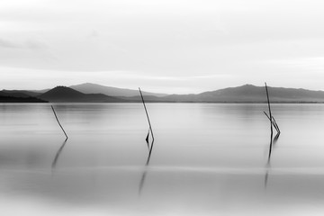 Sunset at Trasimeno lake (Umbria, Italy), with poles on the foreground