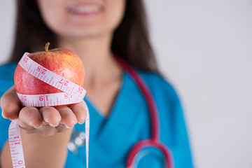 Healthy lifestyle, food and sport concept. Close up Smiling doctor woman hand holding measuring tape around fresh green apple.