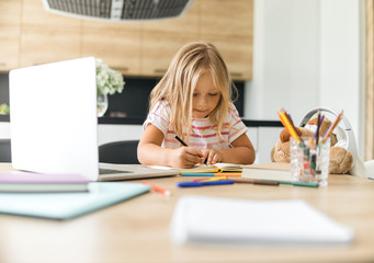 Concentrated kid drawing in notebook stock photo