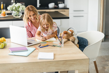 Excited child drawing and mom smiling stock photo