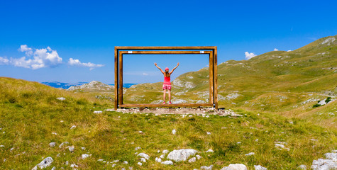 Montenegro, national park of Durmitor in Blakans, famous frame at the top- woman happy in holiday or hiking concept